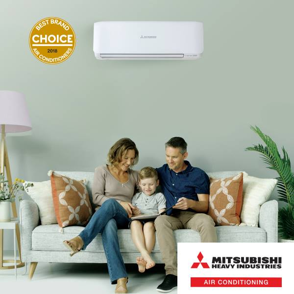Family sitting on a couch with heat pump above
