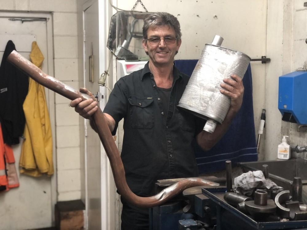 Mechanic standing holding exhaust