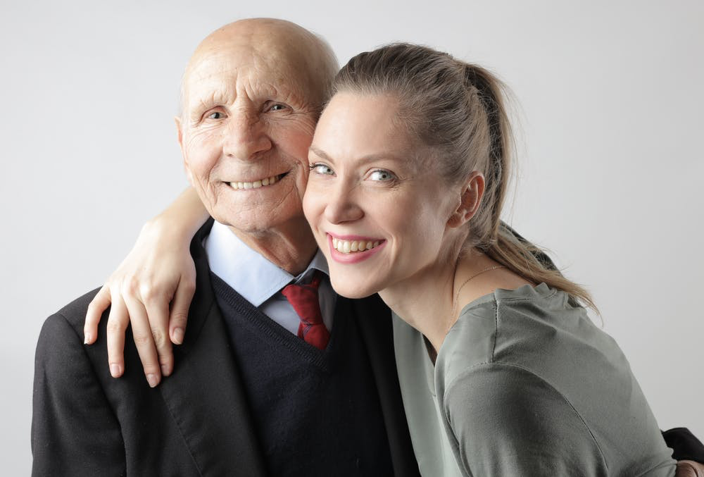 Old man and young woman standing together
