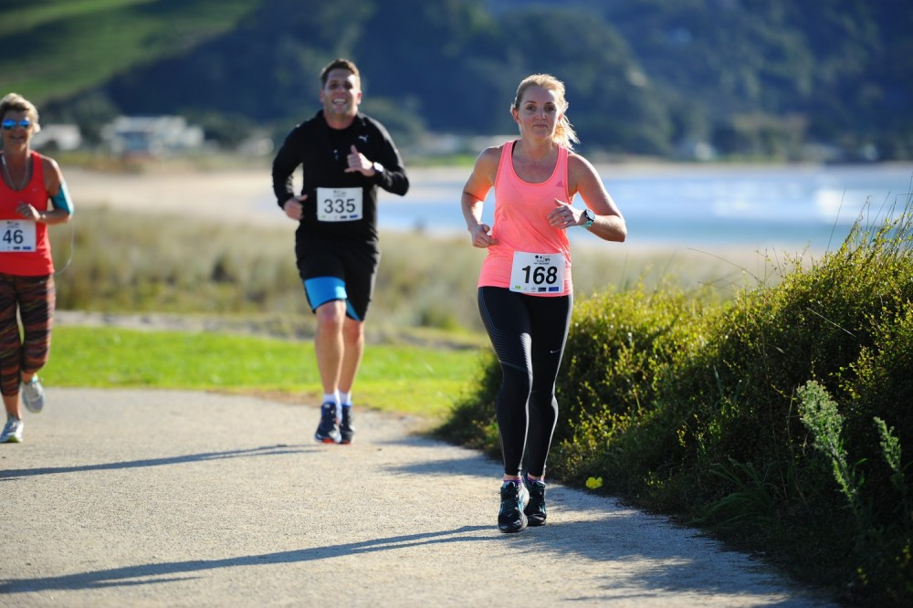 two women running in pink and man running in black on coastal path
