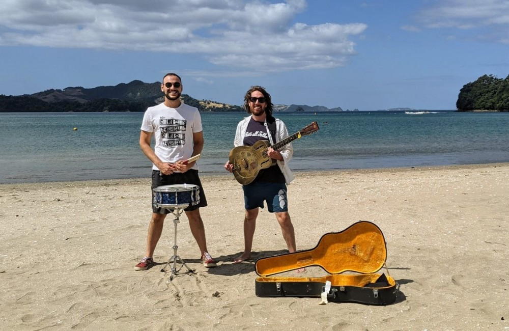 Man standing on the beach with drum kit, man standing on beach with guitar and guitar case