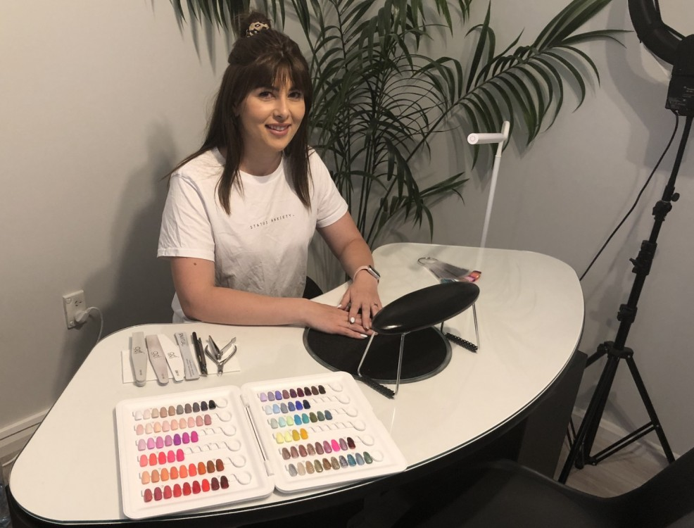 Nail artist sitting at desk ready to do nails