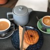 tea pot cup of tea and cup of coffee and donut on table