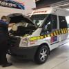 Man under hood of ambulance