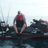 Man sitting on jet ski with fishing rods