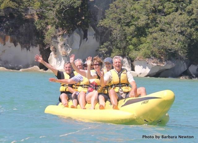 People waving on yellow banana boat
