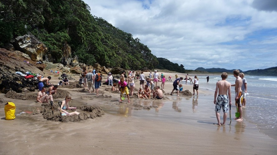 People at Hot Water Beach standing and digging in the sand