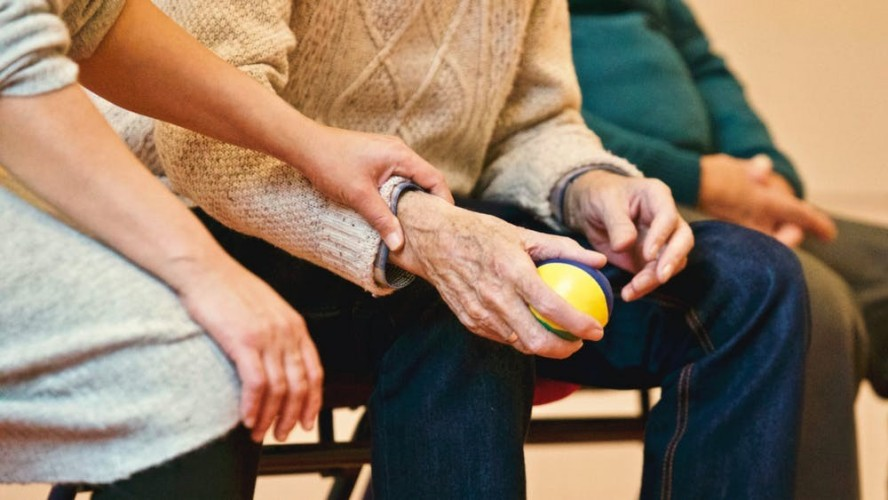 young person holding older persons hand holding a squeeze ball