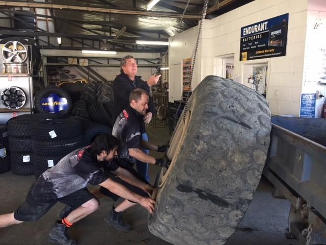 men moving large tyre