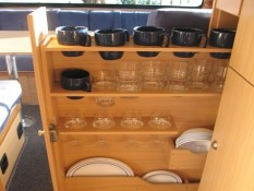 Clever storage solutions in and easy access within campervan kitchen for cups, glasses and cups