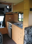 This fully self-contained motorhome kitchen has hot & cold running water, water filter, gas cooking facilities, range hood, fridge and microwave.