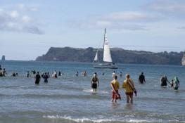Buffalo Beach Polar Swim challenge with Buffalo regatta in background Whitianga