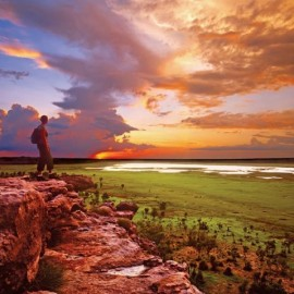 Person standing on cliff at sunset