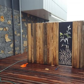 Stone wall of house and timber wall with steel cutout
