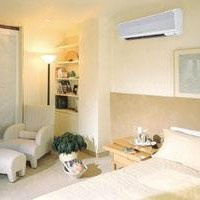 Bedroom with heat pump on wall
