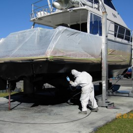 Man in overalls spray painting boat