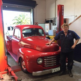 Man standing  in front os red truck of