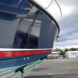 Side of blue boat with stripe