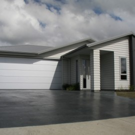 House with oxide black concrete driveway