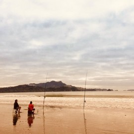 Two people fishing on beach