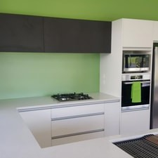 White and black kitchen with green splash back