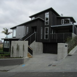 Two storey black house with concrete driveway