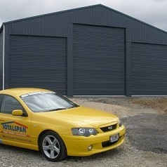 Yellow ute by grey shed