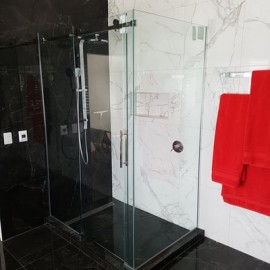 Glass shower in black and white room with red towels