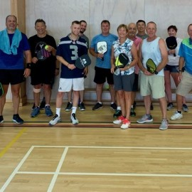 Group standing with pickle ball bats