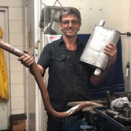 Man holding exhaust pipe
