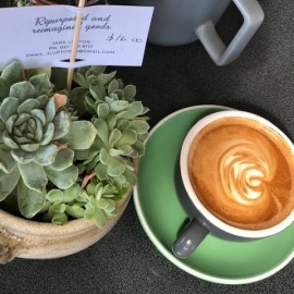cup of coffee next to plant on table