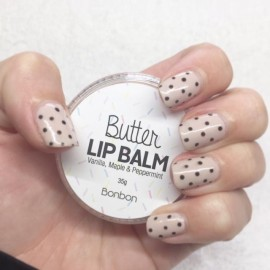 Hand with spotted nails holing lip balm