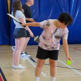 Boy with pickle ball bat and ball