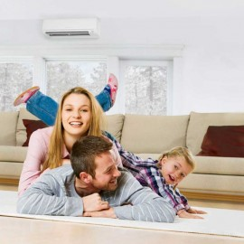 Women, man and child on living room floor with couch and heat pump