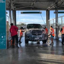 people in hi vis washing car