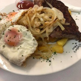 Egg, onions and steak on plate