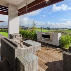 Outdoor fireplace and timber deck looking out to rural views