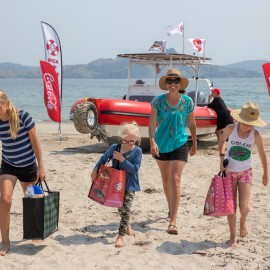 Family taking delivery of groceries on beach