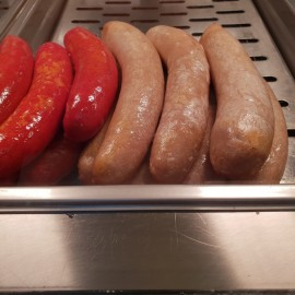 Hot sausages on warming tray in heating cabinet