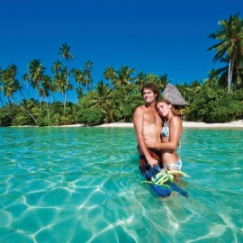 Couple standing in water by tropical island
