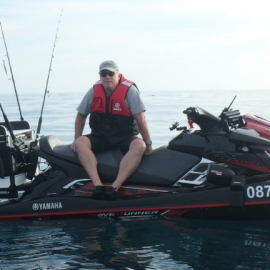 Man sitting on jet ski with fishing rods