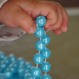 Child holding blue beads