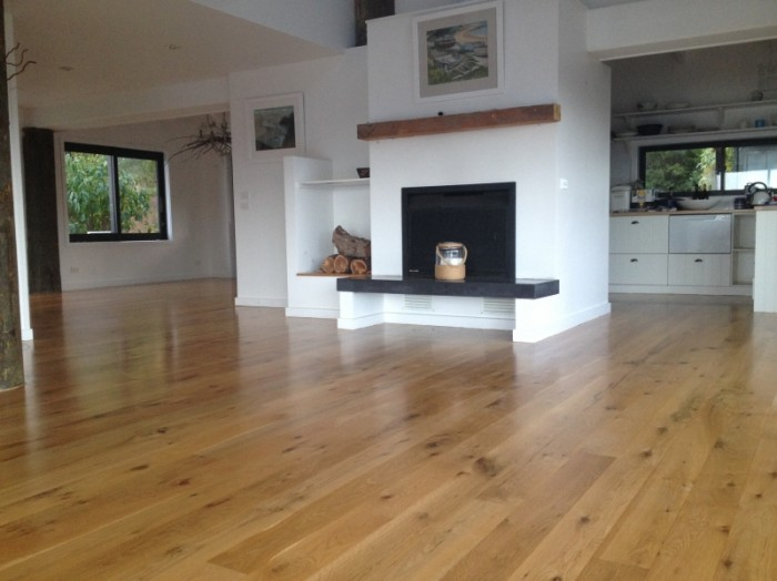 Sun damaged oak floor re-sanded and 4 coats of clear water-based polyurethane applied. Whangapoua.